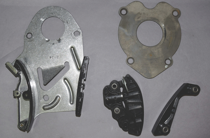 The original thrust plate that included the chain guide and tensioner was replaced by a separate thrust plate, a chain guide and a plastic tensioner with a spring-loaded piston.