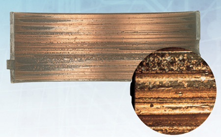 overplated copper alloy bearing gouged by cast iron debris. inset photo shows the microscopic detail of the gouges. f-m photo.