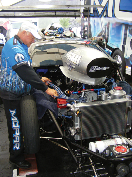 figure 1 - roy johnson, dad and engine builder for nhra?pro stock champ allen johnson, makes adjustments to his pro stock hemi during downtime at summit raceway park in norwalk oh.