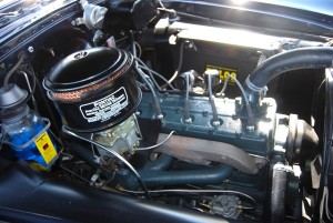 A good example of a detailed engine compartment in a 1954 Pontiac with a straight eight engine. Braided spark plug wires and old style hose clamps would add to the originality, but this is still a nicely done restoration.